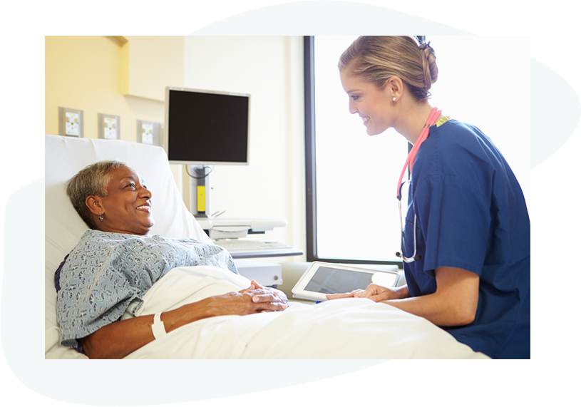 Nurse holding tablet next to patient laying in hospital bed happy of the outcomes of her care