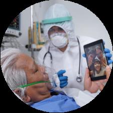 Médecin en combinaison de matières dangereuses aidant le patient infecté à parler avec sa famille alors qu'il est allongé dans un lit d'hôpital