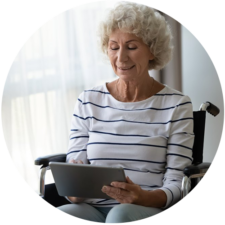 Elderly lady in wheelchair using tablet to read about virtual complex care