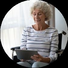 Dame aînée en chaise roulante utilisant une tablette pour lire au sujet des soins complexes virtuels.