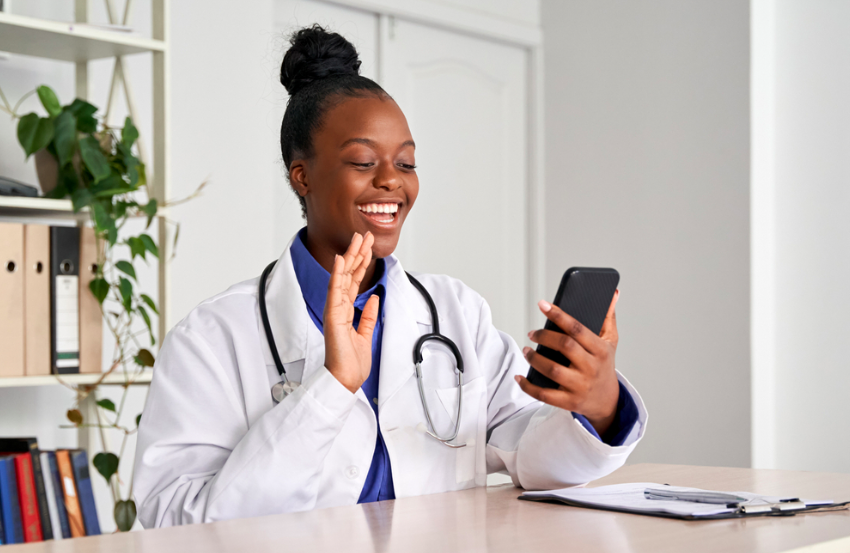 Female doctor waving at patient on video call